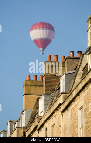 A red and white hot air balloon flies over the rooftops of Bath in southern England - Stock Photo