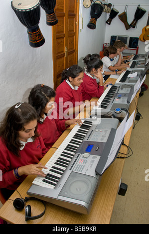 Teenage students practice together on electronic keyboards in school music classroom - Stock Photo