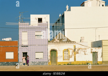 Women gossiping on the doorstep of a house on a street in small fishing village Santa Luzia near Tavira in the Algarve - Stock Photo
