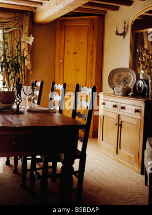 Antique oak table and ladderback chairs in cottage dining room with pine sideboard and tall freestanding corner - Stock Photo