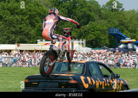 Motorcycle Stunt Rider riding on his Motorbike performing stunts Cowpie Rally Betchworth summer fete Surrey - Stock Photo