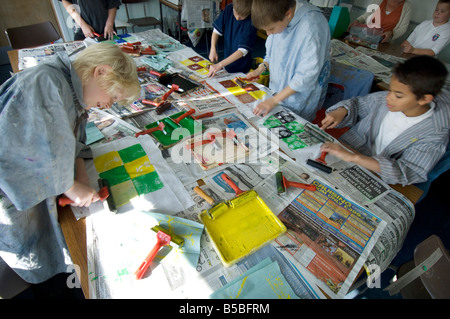 Boys in a schoolroom art class using rollers and paints for textile dying. - Stock Photo