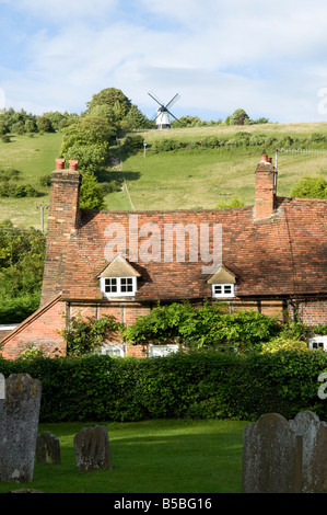Country cottage in a village with a windmill on the hill in the background on a sunny day close up - Stock Photo