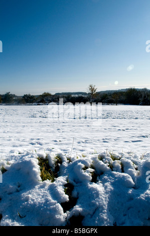 snow during winter looking across a village common towards the trees on a sunny day - Stock Photo