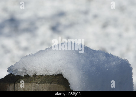 Top of a snow covered gate post in a field - Stock Photo