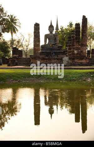 Buddha Statue in Wat Mahathat Temple in Sukhothai Historical park at sunset Thailand - Stock Photo