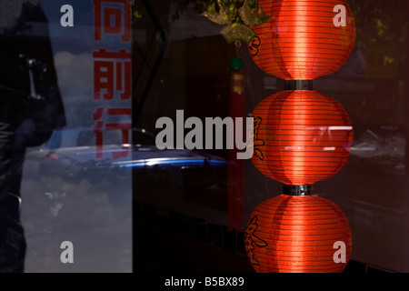 Three red chinese lampshades in the window of a shop in China town in the neighbourhood of Belgrano in Buenos Aires, - Stock Photo