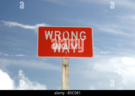 Wrong Way sign against blue sky - Stock Photo