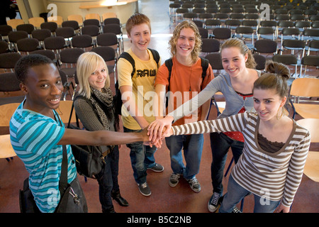 Group portrait of teenage boys and girls in the school hall - Stock Photo