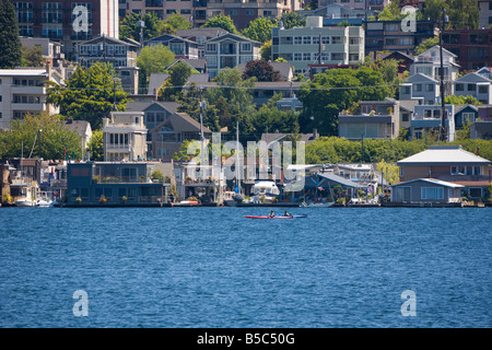 Two kayakers paddle past floating homes in the Eastlake neighborhood on Lake Union in Seattle, Washington - Stock Photo