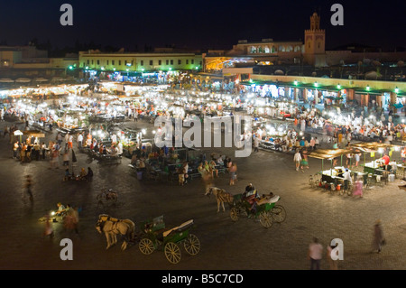 A wide angle aerial view of the busy Djemaa El Fna in Marrakesh at night with slow shutter speed for motion blur. - Stock Photo