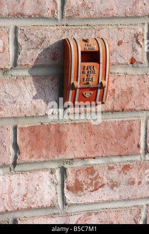 A hotel exterior wall faded fire alarm in the Midwest Pull in case of a fire - Stock Photo
