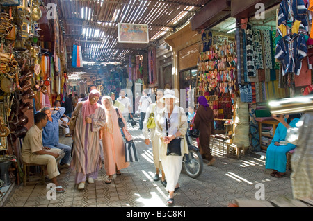 A view of people shopping in the narrow streets of the souk area in Marrakesh. - Stock Photo