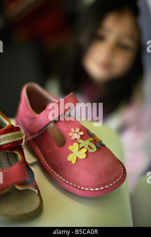 Girl six years old admires shoes in shop window - Stock Photo