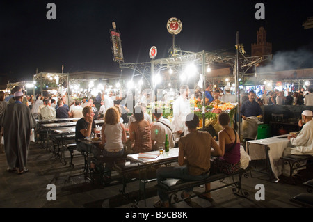 A view of the open air 'restaurants' at the Djemaa El Fna in Marrakesh at night with people eating. - Stock Photo