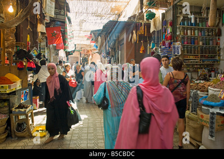 A view of local people shopping in the narrow streets of the souk area in Marrakesh. - Stock Photo