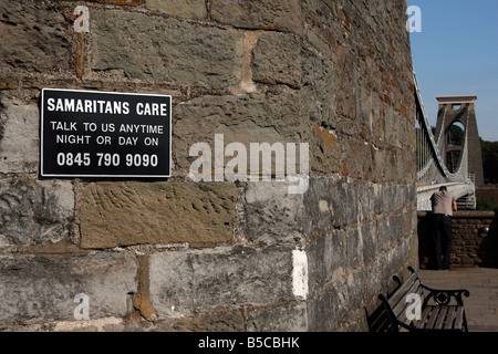 Samaritans sign and suicide helpline on [Clifton Suspension Bridge], lonely man in background, Bristol, England, - Stock Photo