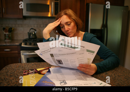 A woman is gripped by worry and anxiety as she looks over her investment statements. - Stock Photo
