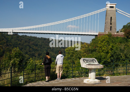 Man and woman stood looking at famous [Clifton Suspension Bridge] from 'The Lookout' over [Avon Gorge], Bristol, - Stock Photo