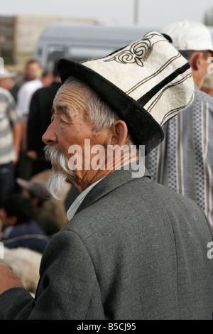 Portrait of old Kyrgyz man wearing traditional hat (kalpak) on Sunday animal market in Karakol, Kyrgyzstan, Central - Stock Photo