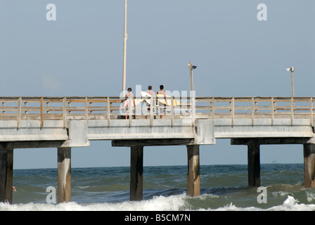 Surfers on the Bob Hall Pier on Padre Island, Texas USA - Stock Photo