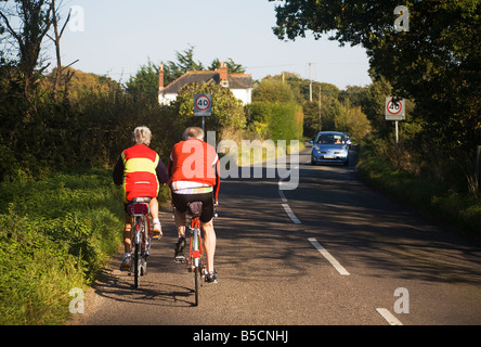 Active adults. Mature couple cycling along a country road on the borders of Hampshire and Dorset. UK. - Stock Photo