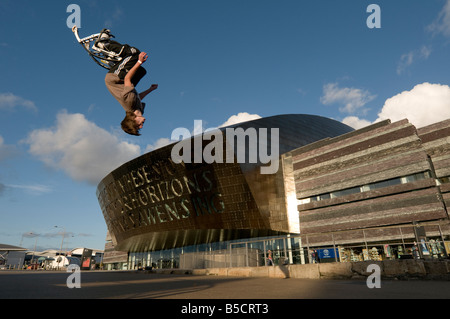 Teenage boy performing somersault acrobatic stunts on bouncy pogo stilts outside the Wales Millennium Centre Cardiff - Stock Photo