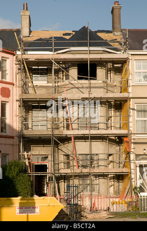 three storey terraced house being renovated covered in scaffolding Aberystwyth Wales UK - Stock Photo