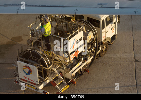 Airport worker refuellling commercial aircraft. Ground support operations in civil aviation. - Stock Photo