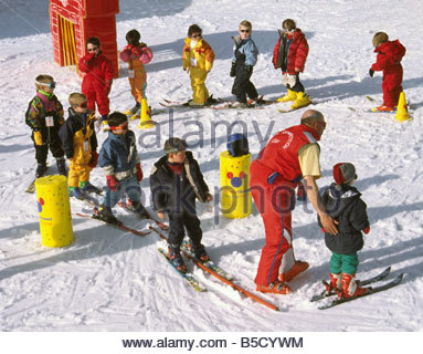 Ski School Instructor Middle Age Male With 11 Young Children On Skies Moving In A Circle Around Obstacles In Snow - Stock Photo