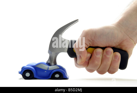 A MODEL CAR HIT AND SQUASHED BY A HAMMER HELD IN A MANS HAND RE CAR DAMAGE RISING INSURANCE COSTS VANDALISM MOTORISTS - Stock Photo