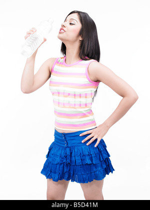 a pretty asian girl of indian origin drinking bottled mineral water - Stock Photo