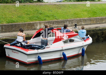 Motorboat Hire Boat with teenagers teenage friends on Boating Day Out in Molesey Lock on the River Thames Molesey - Stock Photo