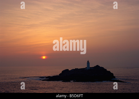 Lighthouse on rock in the sea at sunset at Godrevy Point Cornwall England R Rainford - Stock Photo