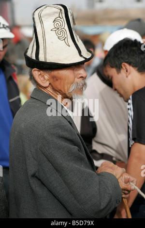 Old Kyrgyz man wearing traditional hat (kalpak) on Sunday animal market in Karakol, Kyrgyzstan, Central Asia - Stock Photo