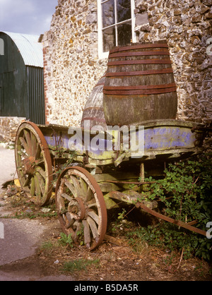 UK England Devon old cider barrels and cart in farmyard - Stock Photo