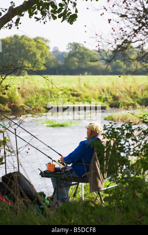 Fisherman fishing on a shady river bank. Warm sunny day in Dorset. UK. - Stock Photo