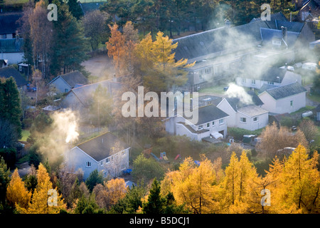 Smoking Chimneys, roofs, with Larch trees in Autumn Foliage.  The Scottish village of Braemar, Aberdeenshire, Cairngorms - Stock Photo