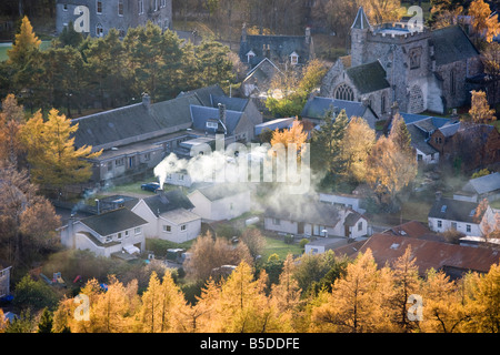 Smoking Chimneys, and roofs, with Larch trees in Autumn season Foliage, in the Scottish village to Braemar, Cairngorms - Stock Photo