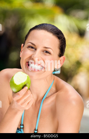 Young woman in bikini holding apple, smiling, close-up - Stock Photo