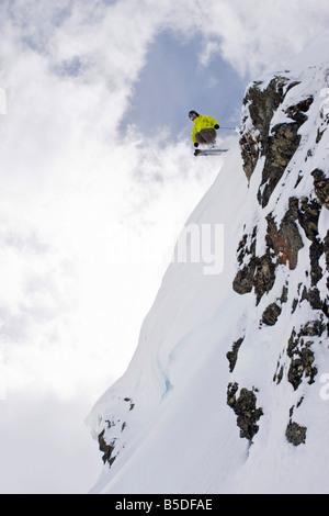 Austria, Tyrol, Zillertal, Gerlos, Freeride skiing, Man doing jump across rock - Stock Photo