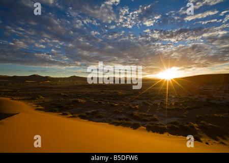 Africa, Namibia, Sun rising over Namib Desert - Stock Photo