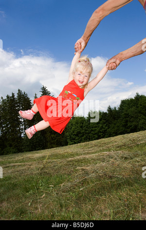 Blonde little girl being swung around, 2 years old, outside - Stock Photo