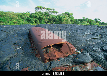 School bus buried in the 1988 basalt lava flows that covered a large area Puna coast, Big Island, Hawaii, USA - Stock Photo
