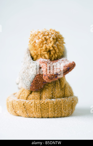 Scarf wrapped around knit hat, snow-covered - Stock Photo