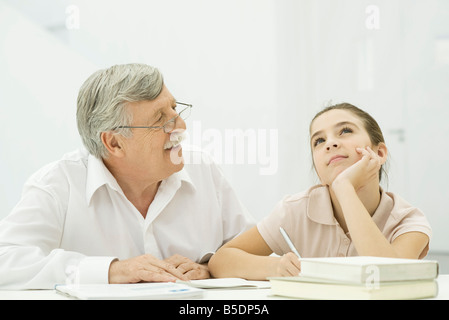 Grandfather helping granddaughter with homework - Stock Photo