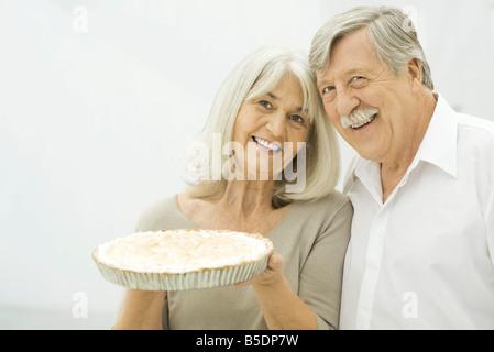 Senior couple smiling, woman holding up pie - Stock Photo