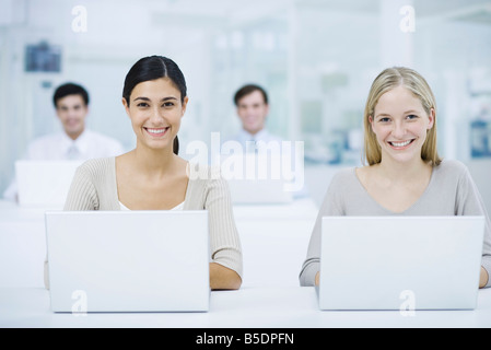 Professional women using laptop computers, smiling at camera, colleagues in background - Stock Photo
