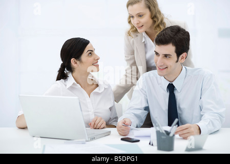 Colleagues gathered around laptop computer, smiling - Stock Photo