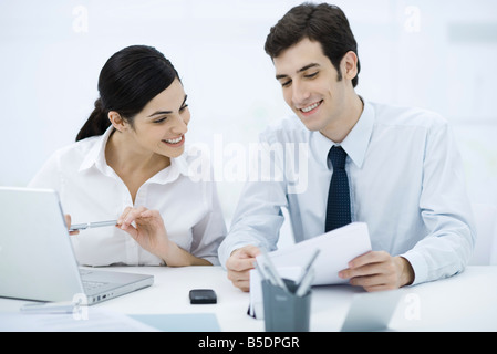 Colleagues sitting together at desk, looking at document, smiling - Stock Photo